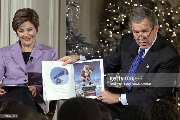 President George W Bush reads ''Twas the Night Before Christmas' to school children in the East Room of the White House as First Lady Laura Bush...