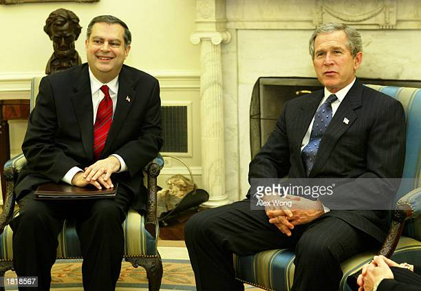 S President George W Bush receives a briefing on carbon sequestration as he meets with US Secretary of Energy Spencer Abraham at the Oval Office of...