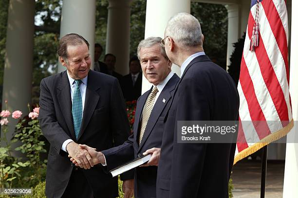 US President George W Bush receives the September 11th Commission report from commission members Thomas Kean and Lee Hamilton in the Rose Garden of...