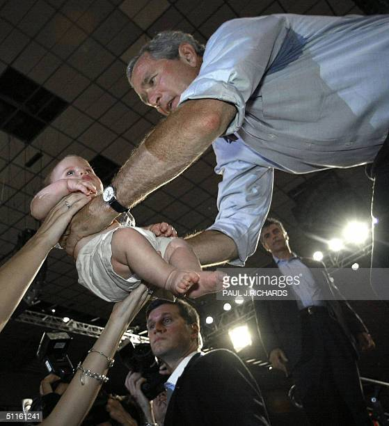 President George W Bush returns Tyler Acton 3months the baby of a supporter inside the Arizona Veterans Memorial Coliseum after delivering a campaign...