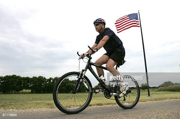 President George W Bush rides his bike on his ranch July 27 2004 in Crawford Texas