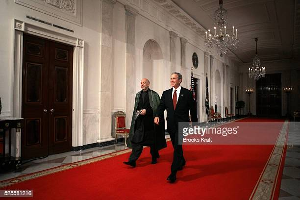 President George W. Bush, right, and Afghan President Hamid Karzai walk toward the East Room of the White House to speak with reporters, May 23,...