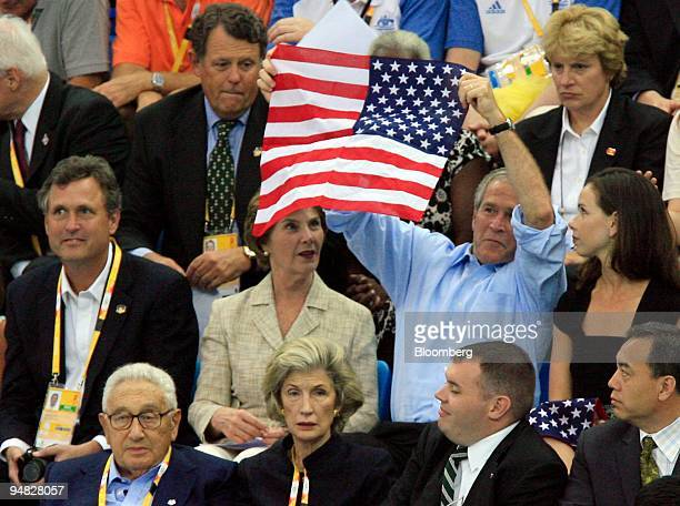 S President George W Bush second right in the second row holds up the American flag as his wife First Lady Laura Bush second row second left and...