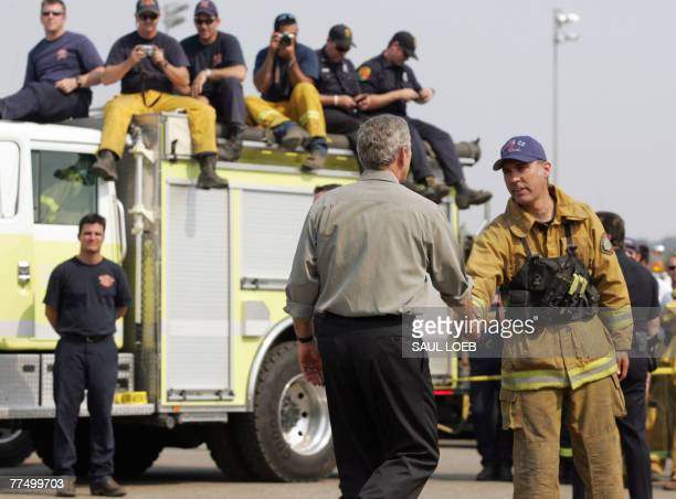 US President George W Bush shakes hands with a first responder after speaking on the Southern California wildfires in Escondido California 25 October...