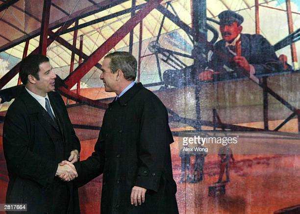 S President George W Bush shakes hands with actor John Travolta at a ceremony of the Centennial Celebrations of the First Flight at the Wright...