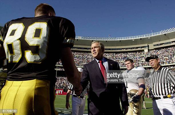 President George W Bush shakes hands with an Army team Captain Clint Dodson before the coin toss 01 December 2001 at the 102nd Army Navy game in...