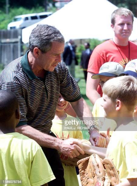 President George W. Bush shakes hands with children attending day camp at Oak Mountain State Park near Birmingham, Alabama, 21 June 2001. Bush...