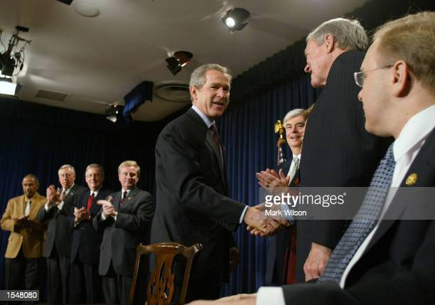 President George W. Bush shakes hands with members of Congress after signing the Martin Luther King Jr. Equal Protection of Voting Rights Act of 2002...