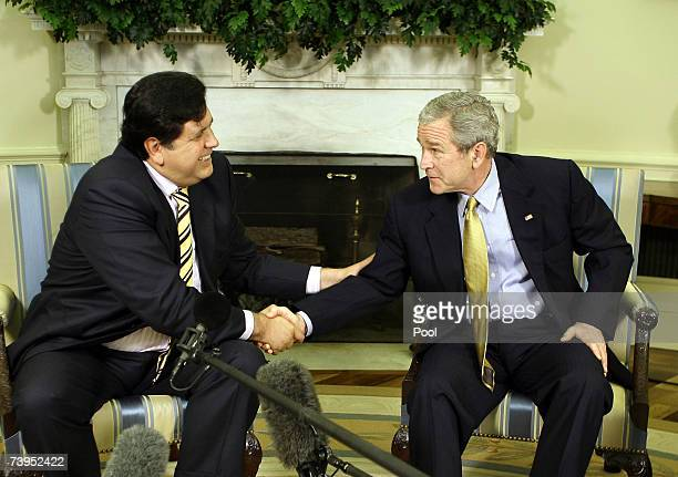 US President George W Bush shakes hands with Peru's President Alan Garcia in the Oval Office at the White House April 23 2007 in Washington DC Garcia...