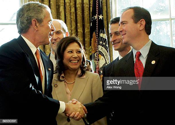 S President George W Bush shakes hands with Rep Adam Schiff as Rep Rick Larsen Rep Hilda Solis and Rep Anthony Weiner look on during a signing...