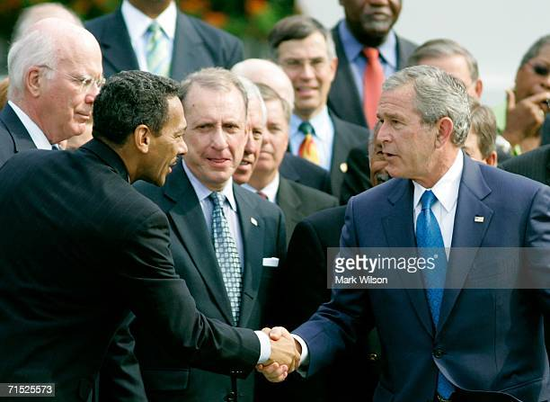 S President George W Bush shakes hands with Rep Mel Watt who is Chairman of the Congressional Black Caucus while surrounded by legislators and civil...