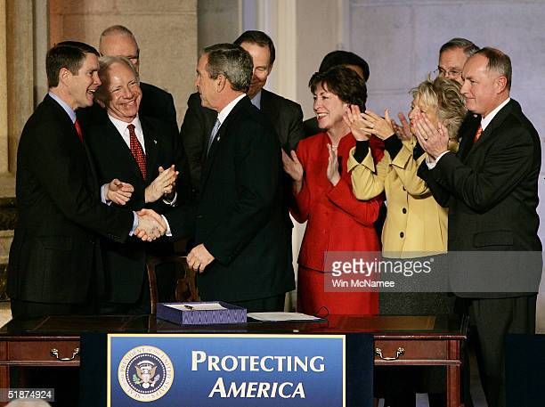 S President George W Bush shakes hands with Sen Bill Frist legislators and administration officials after signing the intelligence reform bill with...