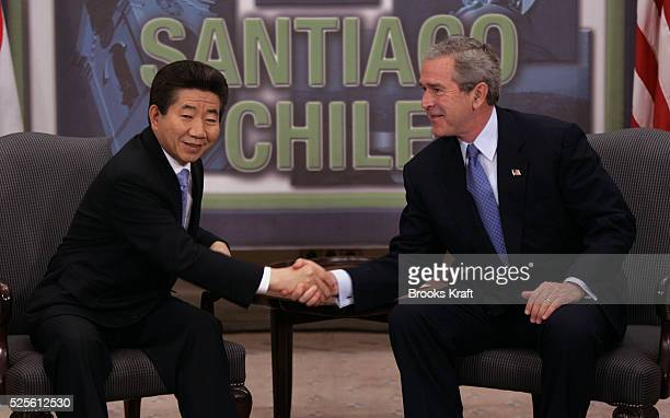 US President George W Bush shakes hands with South Korean President Roh Moohyun during their bilateral meeting at the Asia Pacific Economic...