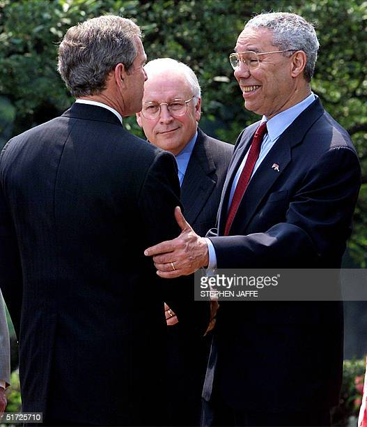 President George W Bush shakes hands with US Secretary of State Colin Powell along with US Vice President Dick Cheney after making remarks on the...