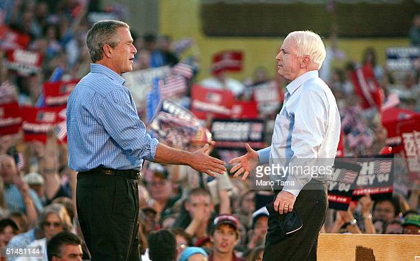 S President George W Bush shakes hands with US Senator John McCain at a Victory 2004 rally at the Jackson County Fairgrounds October 14 2004 in...