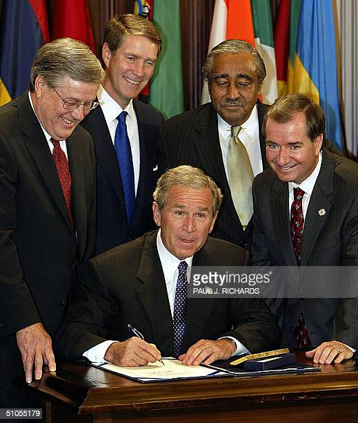 President George W Bush signs 13 July the African Growth and Opportunity Act of 2004 at the Eisenhower Executive Office Building in Washington DC The...