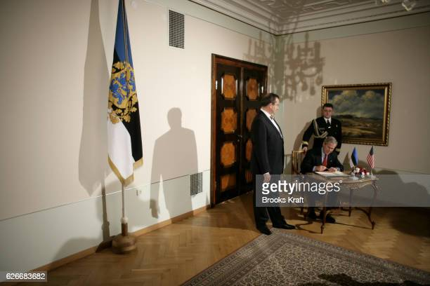 US President George W Bush signs a guest book as Estonian President Toomas Hendrik Ilves looks on at Kadriorg Palace in Talinn Estonia November 28...