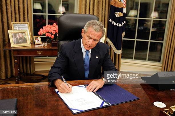 President George W Bush signs a supplemental bill providing relief aid for victims of Hurricane Katrina September 2 2005 in Washington DC Bush got a...