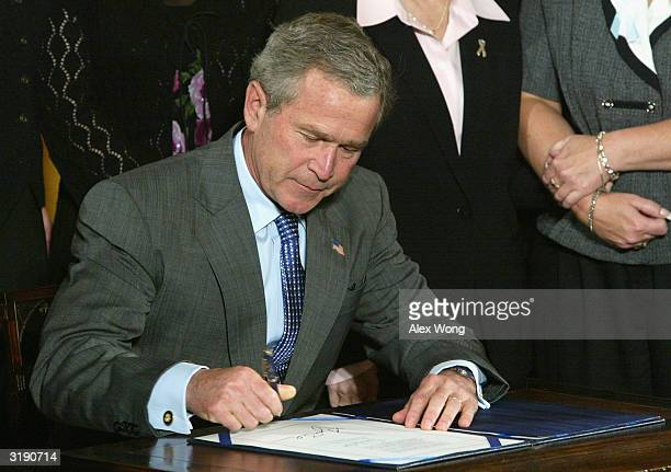 President George W. Bush signs into law the Unborn Victims of Violence Act during a ceremony April 1, 2004 at the East Room of the White House in...