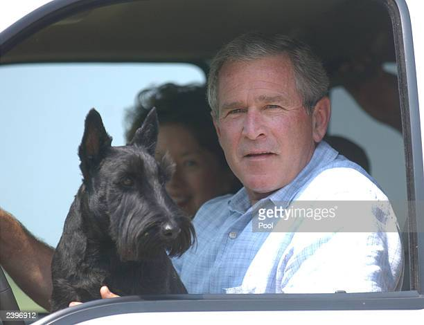 S President George W Bush sits in his vehicle as his dog Barney sits on his lap near his ranch August 13 2003 in Crawford Texas President Bush met...