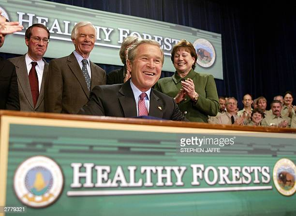President George W Bush smiles after he signed the Healthy Forests Restoration Act of 2003 as US Representative Bob Goodlatte RVA US Senator Thad...
