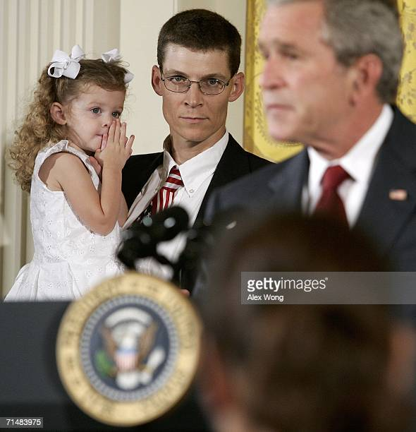 President George W. Bush speaks as members of Gillingham Family of Prather, California, look on during an East Room event on stem cell research...