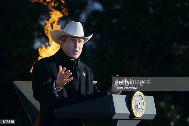 President George W Bush speaks to an Olympic delegation as the Olympic Flame burns in the background December 22 2001 on the South Lawn of the White...