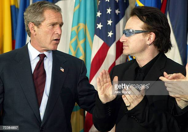 US President George W Bush speaks with Bono the lead singer of Irish pop group U2 March 14 2002 during an InterAmerican Development Bank event on...