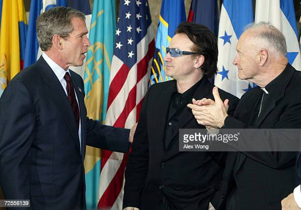 US President George W Bush speaks with Bono the lead singer of Irish pop group U2 as Archbishop of Washington Cardinal Theodore E McCarrick looks on...