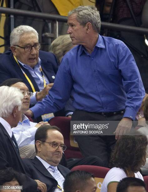 President George W. Bush speaks with former US Secretary of State Henry Kissinger before the start of the men's preliminary round group B basketball...