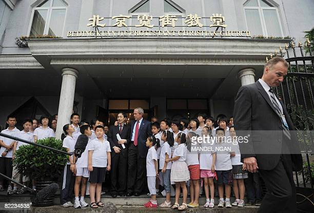 US President George W Bush stands next to Pastor Li JianAn and the children's choir as he speaks after attending Sunday service at Beijing Kuanjie...