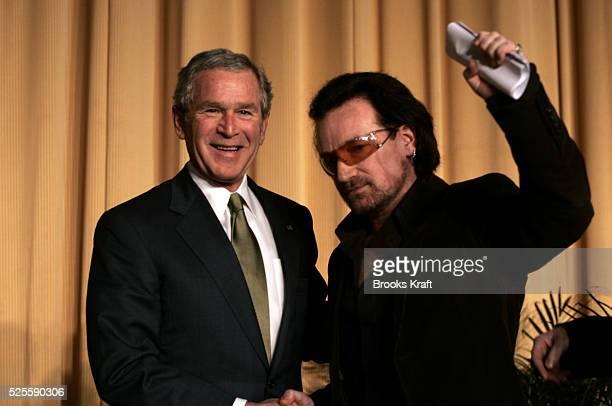 US President George W Bush stands with Irish rock star Bono after Bono spoke at the National Prayer Breakfast in Washington Bush addressed the...
