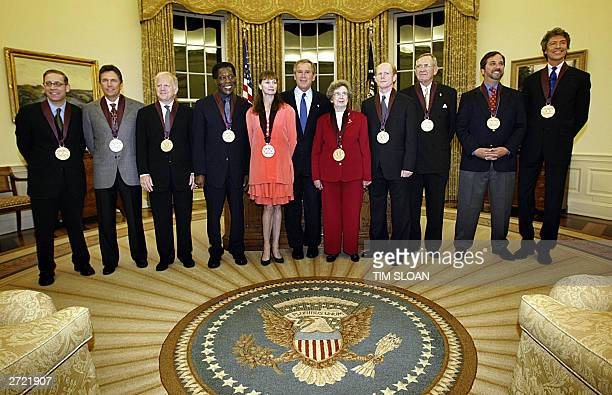 President George W Bush stands with receipients of the National Medal of Arts 12 November 2003 in the Oval Office of the White House in Washington DC...