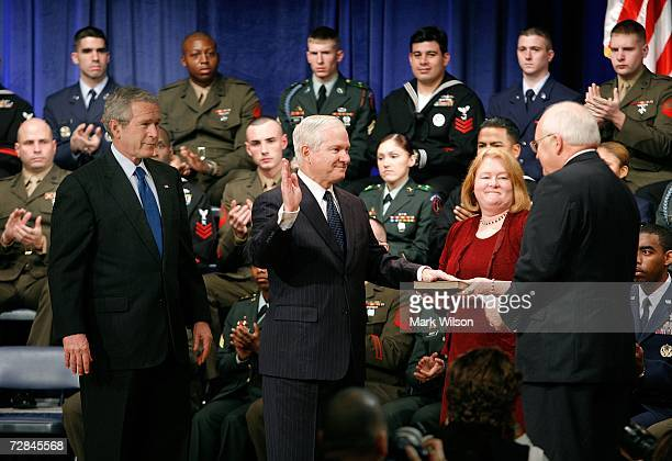 President George W Bush stands with Robert Gates as he raises his right hand and is sworn as Defense Secretary by Vice President Dick Cheney while...