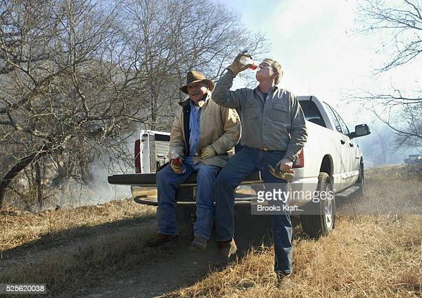 US President George W Bush takes a break with Ken Engelbrecht after clearing and burning cedar underbrush on the Bush Ranch in Crawford Texas Bush...