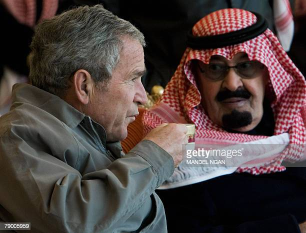 US President George W Bush takes a sip of his tea as he and Saudi King Abdullah bin Abdul Aziz alSaud view the latter's horses 15 January 2008 at the...