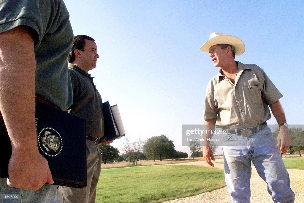 U.S. President George W. Bush talks with Deputy Chief of Staff Joe Hagin and deputy press secretary Scott McClellan on August 6, 2001 at his ranch in Crawford, Texas.