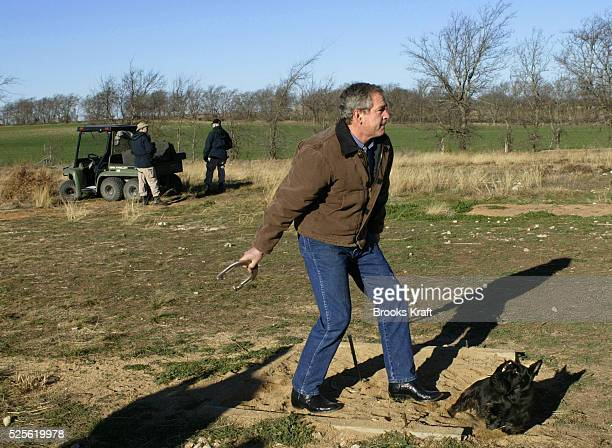 US President George W Bush throws a horseshoe after receiving his daily intelligence briefing on the Bush Ranch in Crawford Texas
