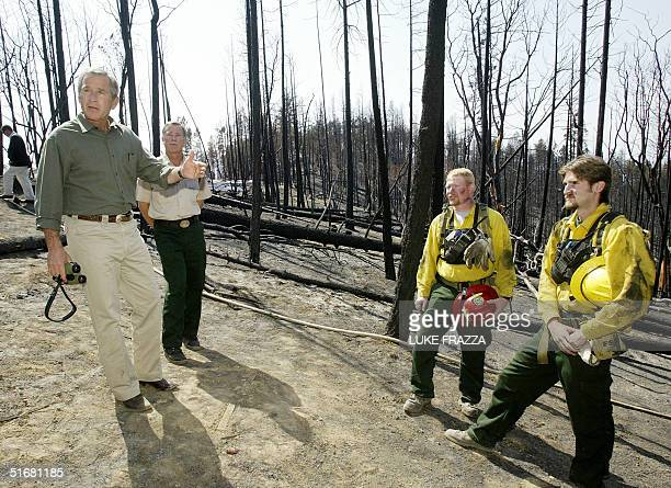 President George W Bush tours the Squires Mountain fire site in Ruch Oregon 22 August 2002 Bush unveiled the Healthy Forests Initiative a plan aimed...