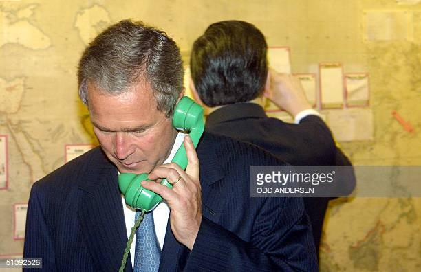 President George W. Bush tries a telephone in the map room of Winston Churchill's Cabinet War Rooms in London 19 July 2001. The American President is...