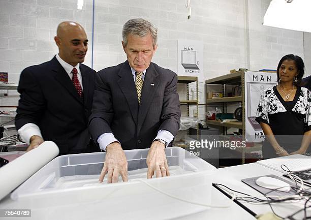 President George W. Bush tries his hand at a submerged waterproof computer keyboard at Man & Machine, Inc. July 18, 2007 in Landover, Maryland....