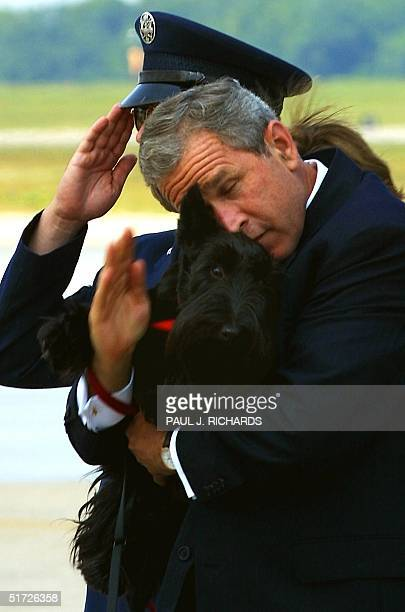 President George W Bush tries to salute the security officers at the steps of Air Force One as he holds his dog Barney after returning from a speech...