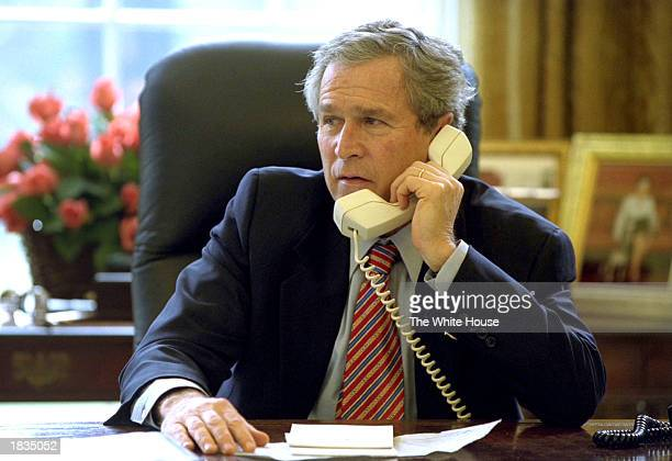 S President George W Bush uses a telephone to speak with British Prime Minister Tony Blair while in the Oval Office at the White House March 7 2003...