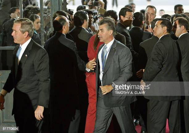 President George W. Bush walks away with his Secret Service agent after intervening to get him into the building after he was blocked from entering...