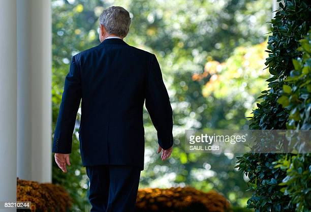 US President George W Bush walks back to the Oval Office after speaking on the status of the US and global economy in the Rose Garden of the White...