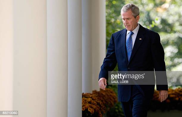 US President George W Bush walks down the West Wing Colonnade as he arrives to speak on the status of the US and global economy in the Rose Garden of...