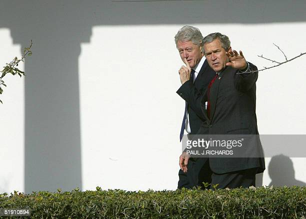 President George W Bush walks in the Colonnade of the White House 03 January 2005 in Washington DC with his predecessor former US president Bill...