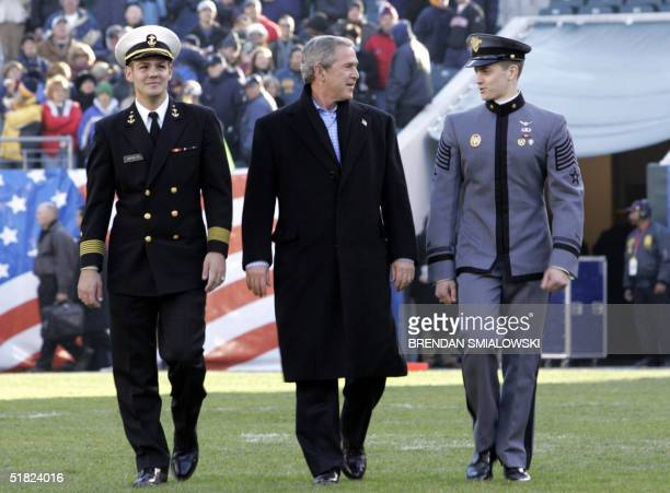 President George W Bush walks onto the field with Travis Amerine Naval Academy captain of the brigade and Ryan Boeka West Point Cadet First Captain...