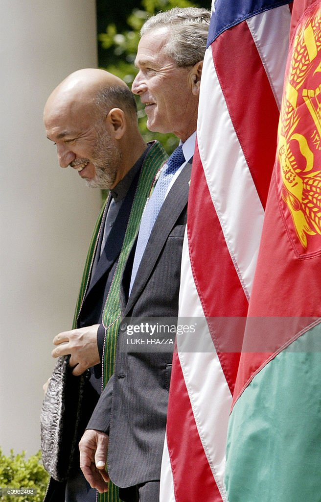 US President George W. Bush (R) walks with Afghan President Hamid Karzai (L) prior to speaking to reporters in the Rose Garden of the White House 15 June 2004 in Washington, DC. Bush announced that the United States and Afghanistan would pursue a bilateral trade deal. AFP PHOTO/Luke FRAZZA