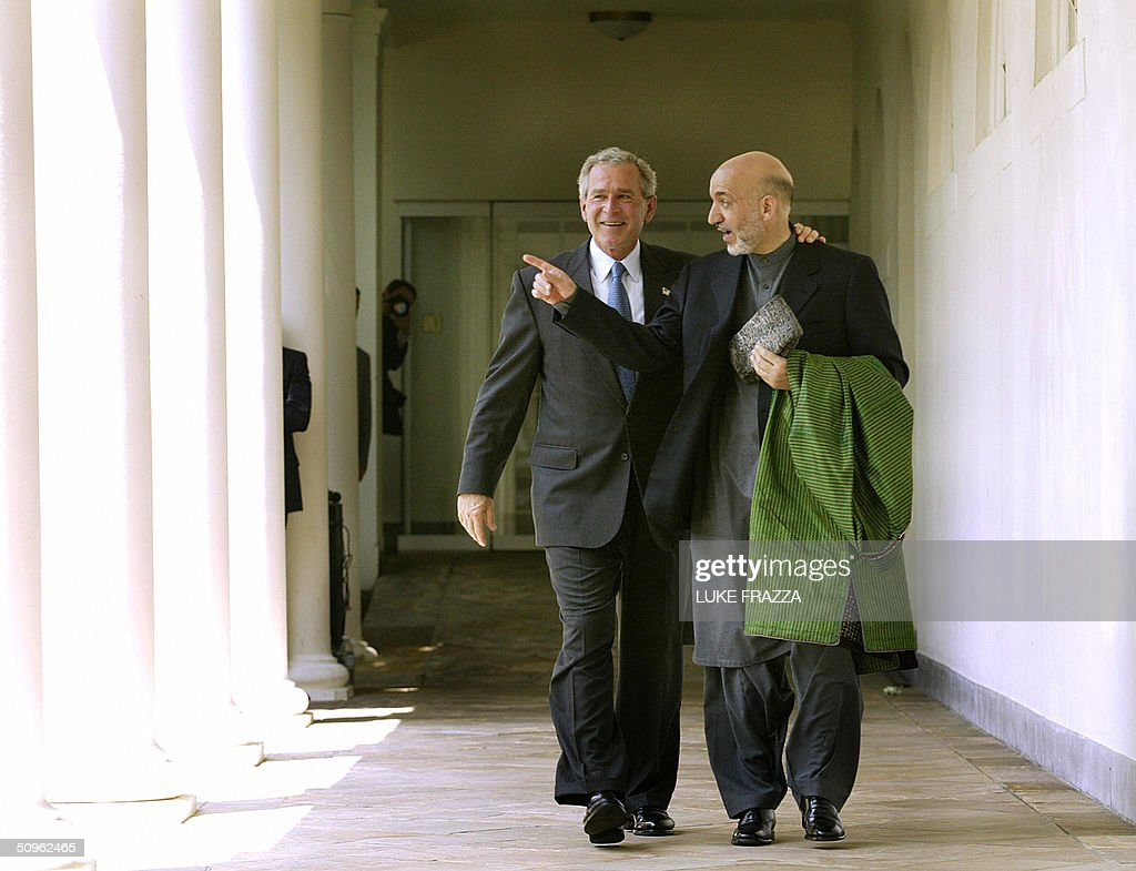 US President George W. Bush (L) walks with Afghan President Hamid Karzai (R) after speaking to reporters in the Rose Garden at the White House 15 June 2004 in Washington, DC. Bush announced that the United States and Afghanistan would pursue a bilateral trade deal. AFP PHOTO/Luke FRAZZA